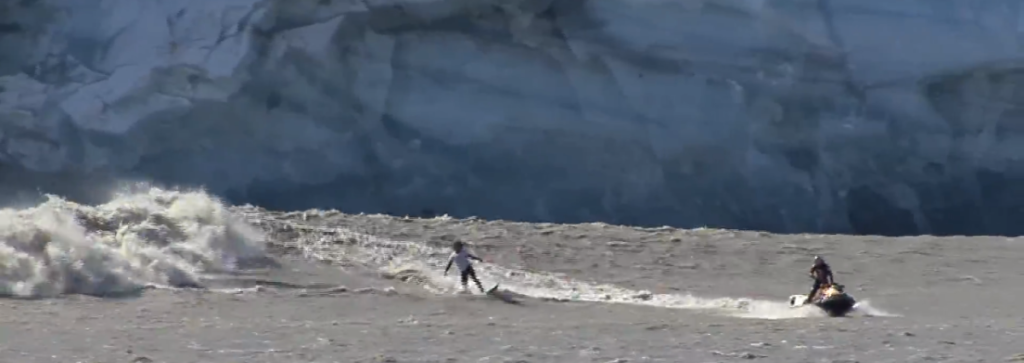 In 2007 at Alaska's Childs Glacier, Kealii Mamala (on surfboard) and Garrett McNamara (on jetski) became the first, and probably only, people to surf a wave made by calving glacier ice. (Ryan Casey/YouTube still)