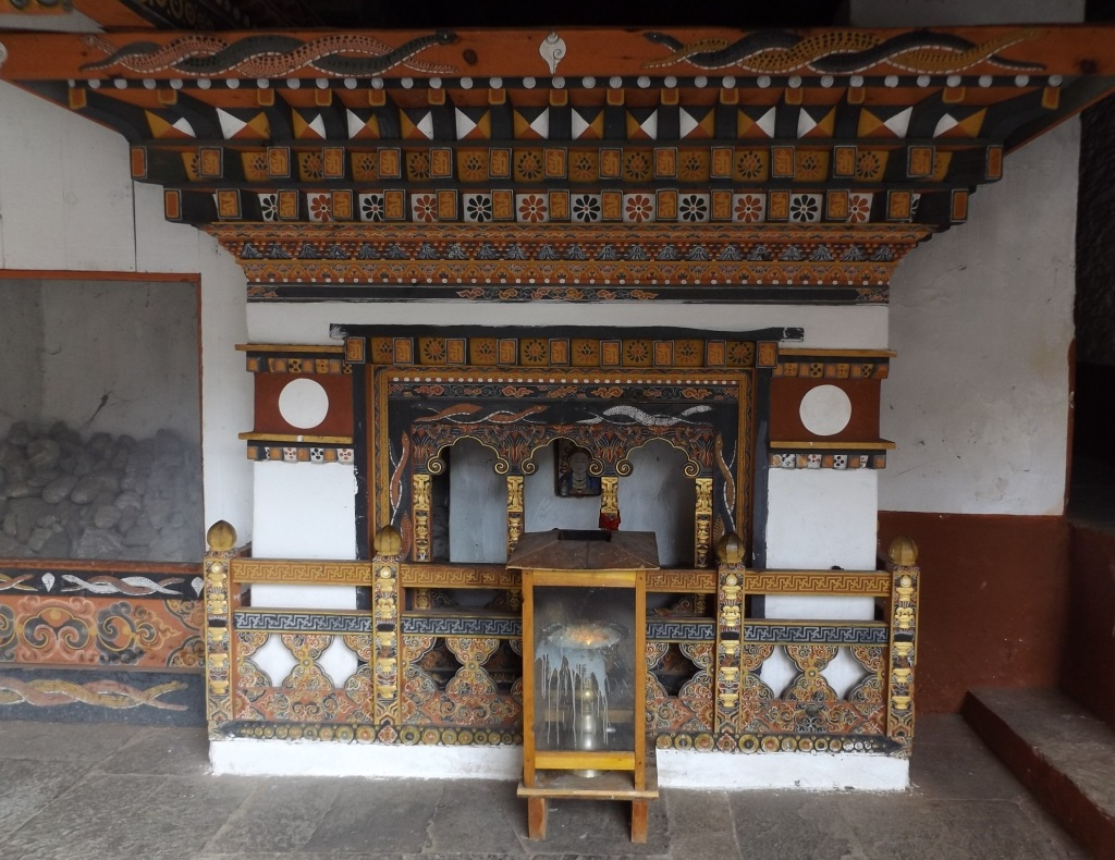 Punakha dzong shrine to Tsomem, with butter-lamp in front and rock offerings to the side. (photo: Ben Orlove)