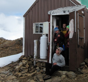 A group of eager students waits at the door of a camp cookshack for a helicopter to land, delivering fresh food, new faculty, and a few letters from home. Photo by Allen Pope