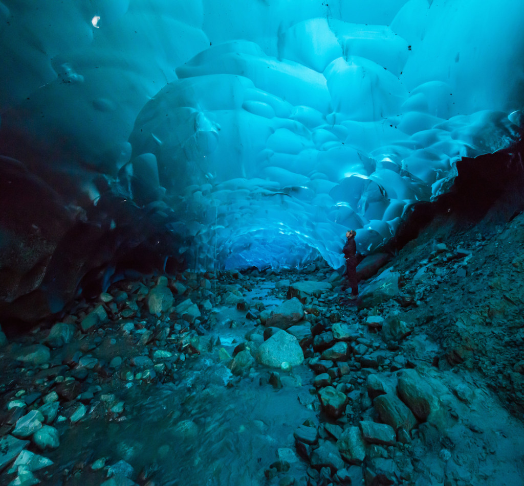 image of a women standing inside an ice cave in the Mendenhall Glacier, Juneau, Alaska