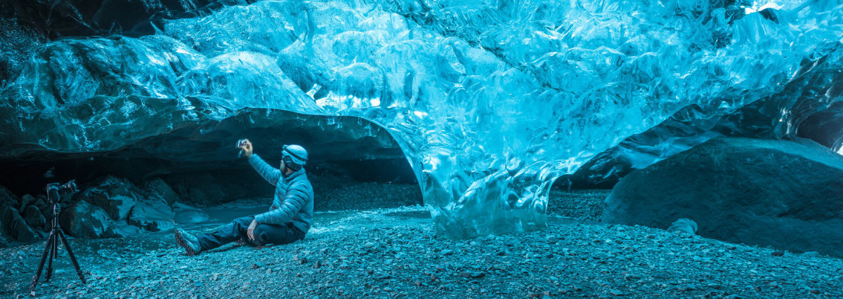 An image of a man taking a photo inside an ice cave