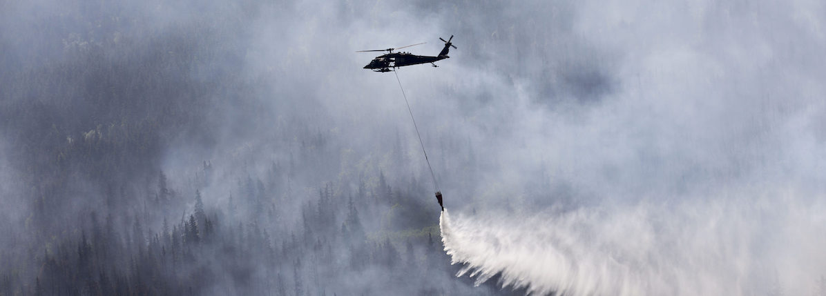 An Alaska Army National Guard helicopter drops approximately 700 gallons of water on to the Stetson Creek Fire near Cooper Landing, Alaska, June 17.