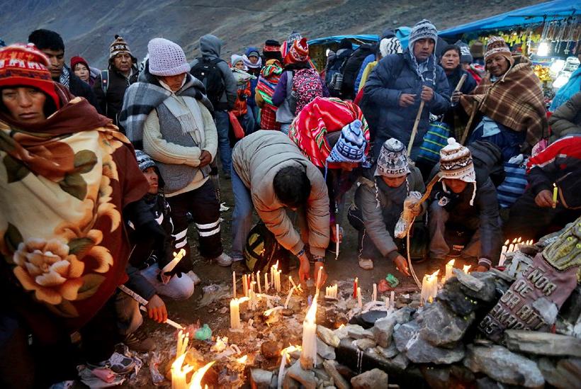 Lighting ceremonial candles at Quyllur Rit'I.