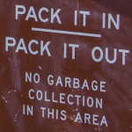 "Sign reads, ""PACK IT IN PACK IT OUT: NO GARBAGE COLLECTION IN THIS AREA"