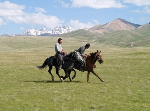 two men on horseback in Kyrgyzstan, with glaciers in background
