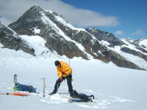 Ben Palto, doctoral student, drills a hole with an ice auger to place an ablation stake for monitoring melt on the Zillmer Glacier.