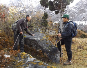 Renzin, pointing out the impression of the book on a boulder to Kinga source: Ben Orlove)
