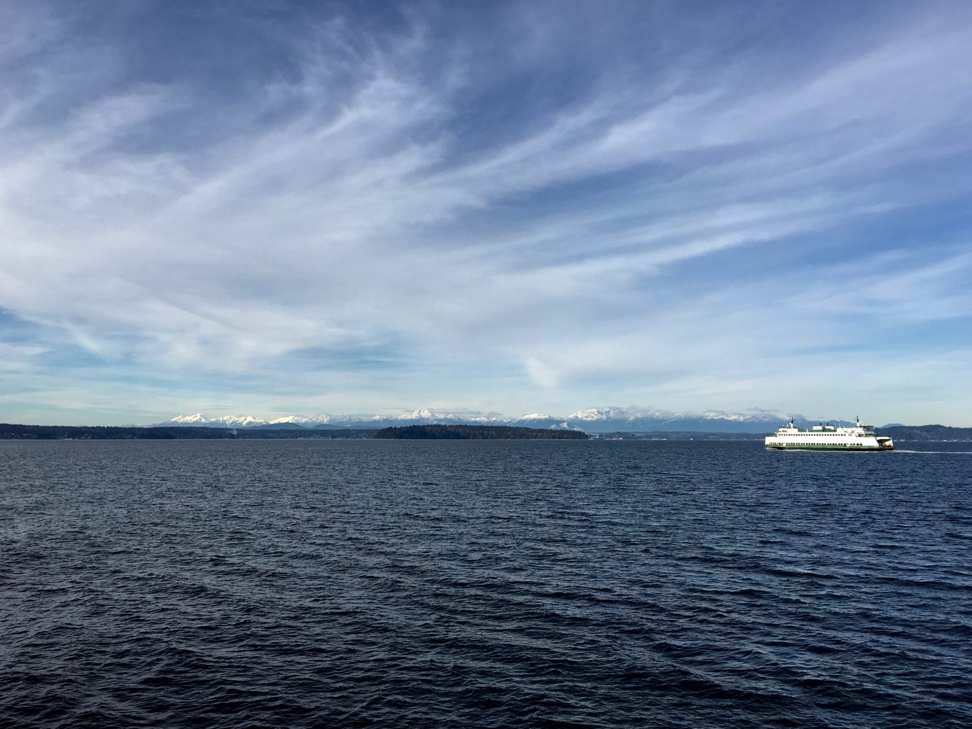 Glaciers atop The Olympic Mountain Range over the Puget Sound and WA State Ferry.