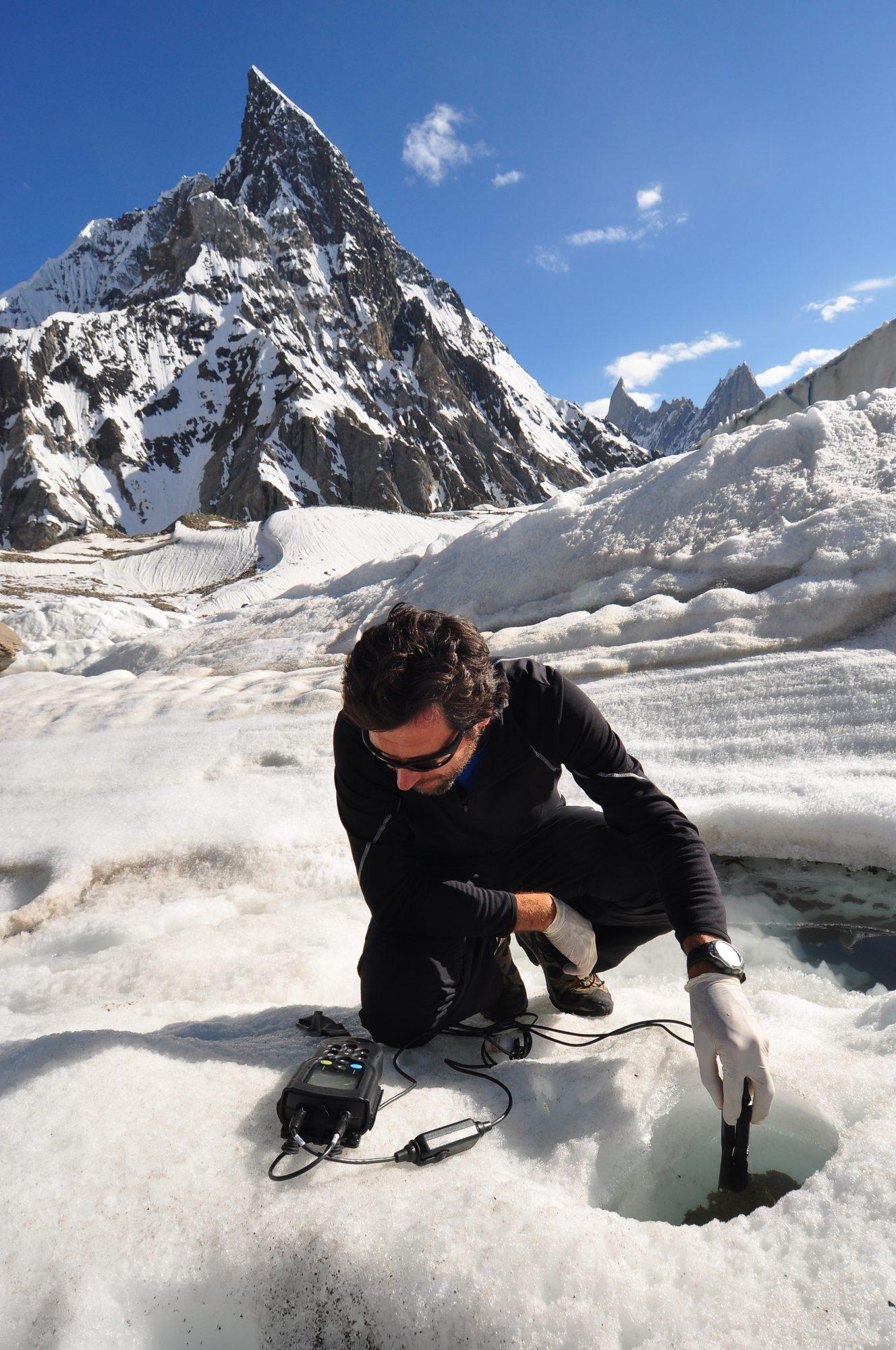 Dr. Roberto Ambrosini taking measurements in cryoconite hole on Baltoro Glacier with Mitre Peak in the background.