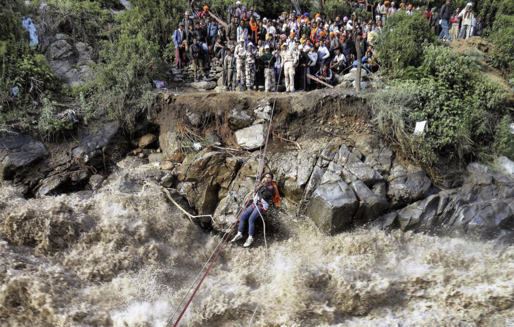 Stranded pilgrims cross a river swollen by GLOF waters in Uttarakhand, India (Source: AP)