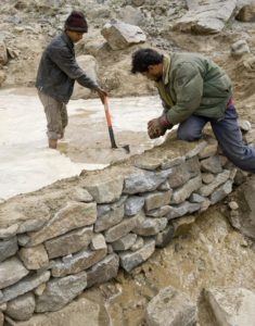 Two locals damming a stone embankment that will serve as an artificial glacier the Ladakh region.