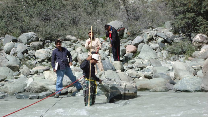 River monitoring experts of the Pakistan Meteorological Department plant a river flow gauge in flood-prone Bagrot river
