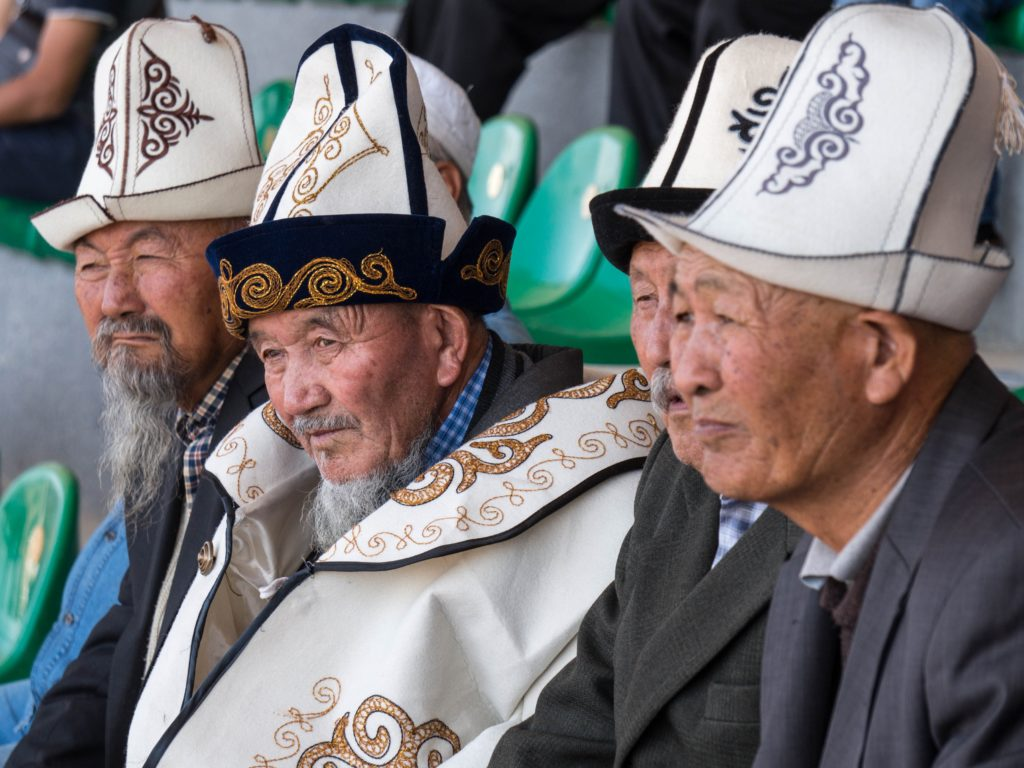 Kyrgyz men in traditional hats, watching the games (source:Ronan Shenhez/Flickr)