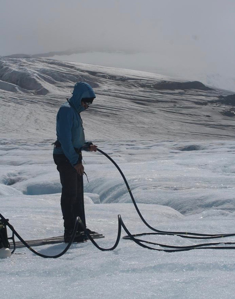A glaciologist uses a steam drill to make a hole in the ice of the Cook Ice Cap to set up an ablation stake (Source: Vincent Favier).