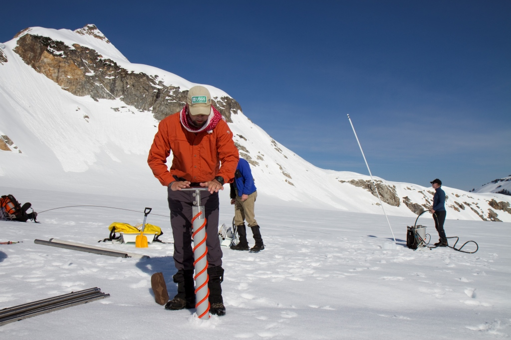 A researcher collecting a snow core sample from South Cascade Glacier (Source: USGS)