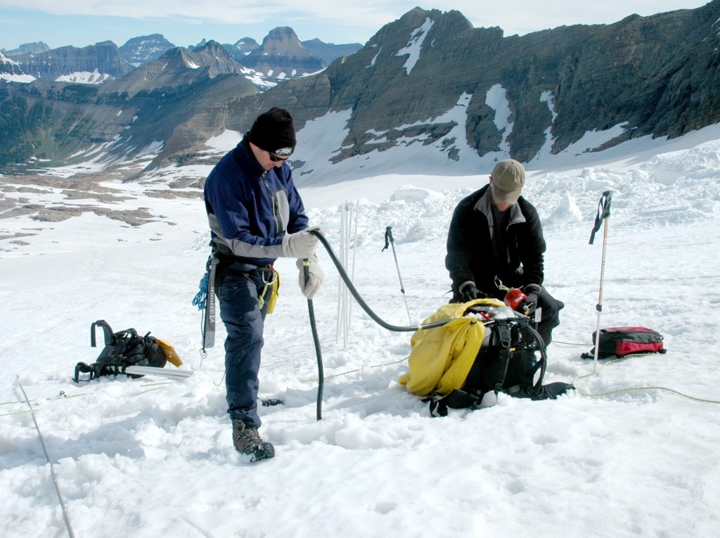 Researchers inserting ablation stakes using a steam drill (Source: USGS)