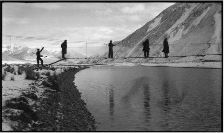 Crossing a swing bridge over the Rangitata River. Kent, Thelma Rene. Ref: 1/2-009844-F. Alexander Turnbull Library. Permission of the Alexander Turnbull Library, Wellington, New Zealand, must be obtained before any re-use of this image.