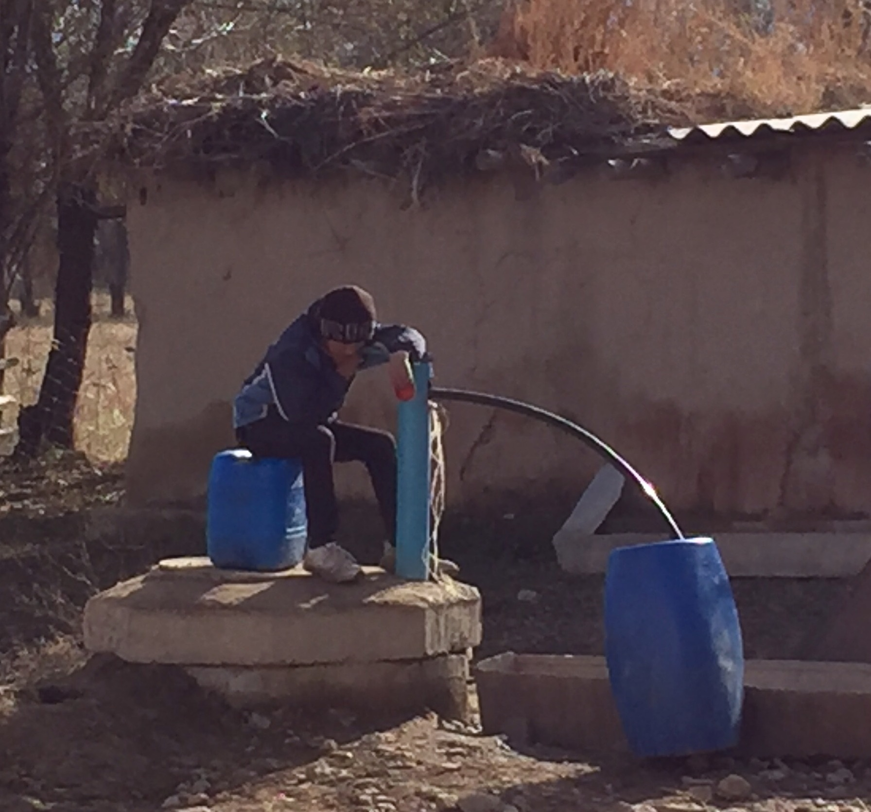Boy filling water containers at a village well, upper Naryn Valley, November 2016 (source: B. Orlove)