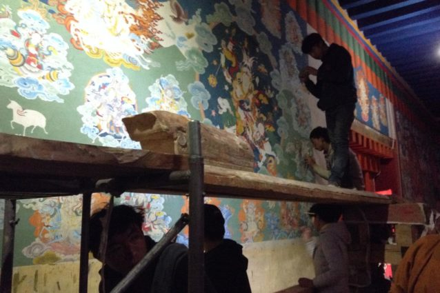 Restoration at Guru Gyam currently taking place with artists hired from Kham, meticulously painting wall murals under the direction of a master painter.(Source: Emily Yeh/University of Colorado).