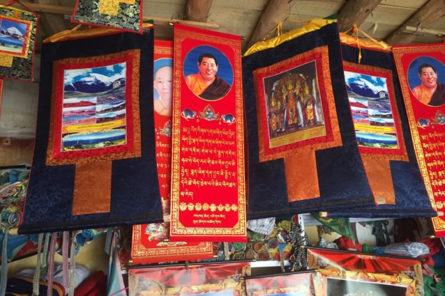 The town of Tarchen is the starting point for circumambulations of Mount Kailash. In the market one can find prayer flags, incense, thangkas, and other religious items, as well as jewelry and clothing. Here a shop displays prints with Khenpo Jigphun's injunction for Tibetans to speak Tibetan, as well as prints of Gendun Choepel. Though Khenpo Jigphun's influence is greatest in Kham and Gendun Choepel was from Amdo, theiir presence is also here in the far western part of Tibet. Many of the shop-keepers are from Markham and other parts of Kham ((Source: Emily Yeh/University of Colorado).