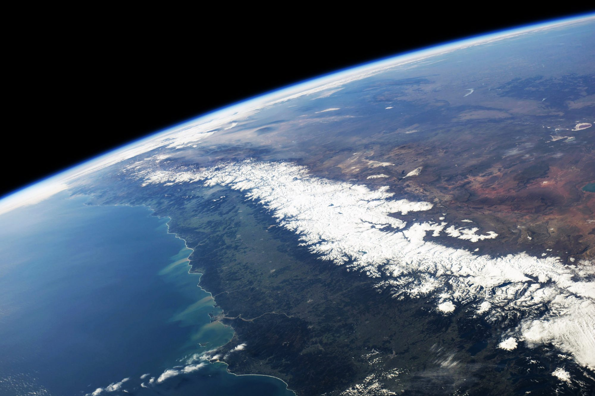 Looking up the Pacific coast of South America at the snow-covered Andes Mountains, which contains the world's largest glaciated area of the tropics (Source: Stuart Rankin/Flickr).