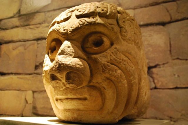"The sculpted head represented the Chavín culture, considered one of the oldest ""civilizations"" in the Americas [BSO explain this--sculpted head of mythological being at Chavin.](source: Boring Lovechild / Flickr)."