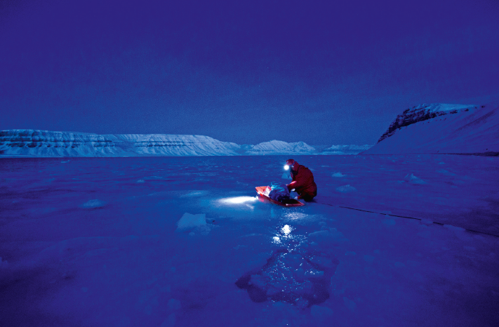 A researcher collecting newly-formed sea ice from Tempelfjorden, Svalbard (Source: Jago Wallenschus)