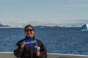 Glaciologist Beatriz Recinos in Greenland, waving the Salvadoran flag