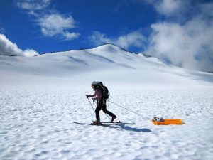 the glaciologist Celeste Labedz is using cross-country skis to bring equipment on a sled across a glacier.