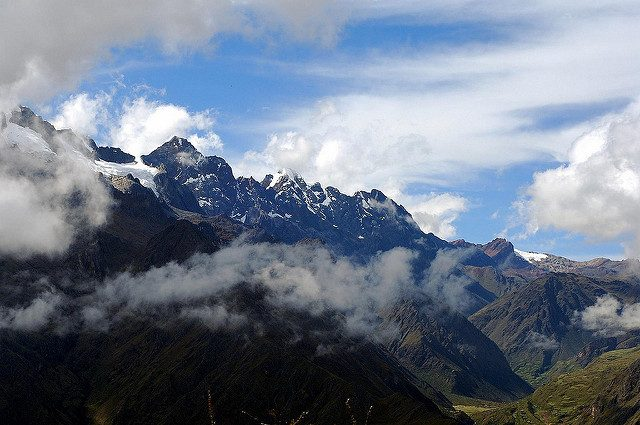 Snowy mountain peaks on the Andes mountains in Peru, surrounded by beautiful fluffy clouds.
